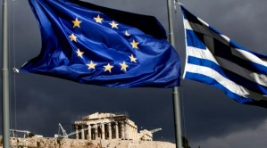 "A European Union (EU) flag, left, and Greek national flag fly near the Parthenon temple on Acropolis hill in Athens, Greece, on Monday, Oct. 31, 2011. Europe's plan to solve the region's debt crisis made credit-default swaps covering Greece ""ineffective,"" Moody's Investors Service said. Photographer: Angelos Tzortzinis/Bloomberg via Getty Images"